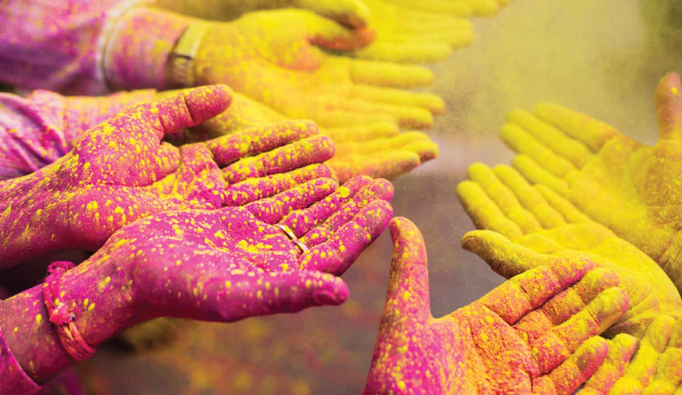 Gathered hands with pink and yellow paint