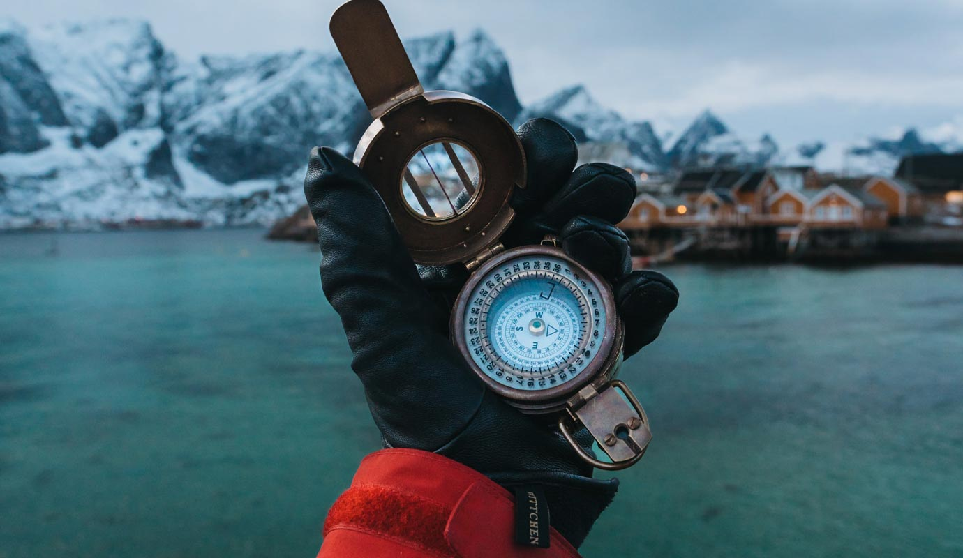 Gloved hand holding a compass