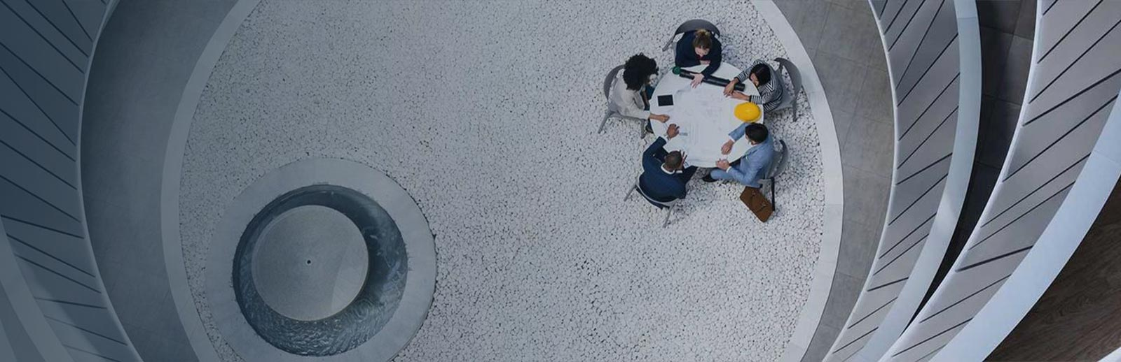 An overhead view of five people sitting around a circular table