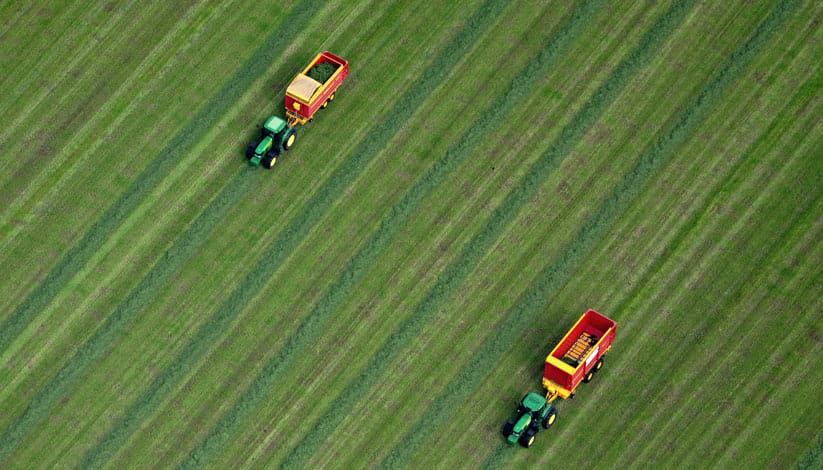 An aerial view of two tractors on farmland