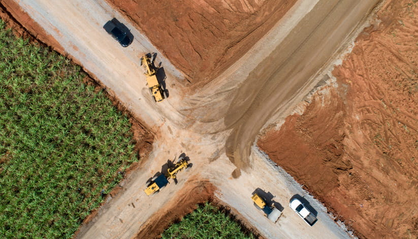 An aerial view of work vehicles on a crossroads on a farm