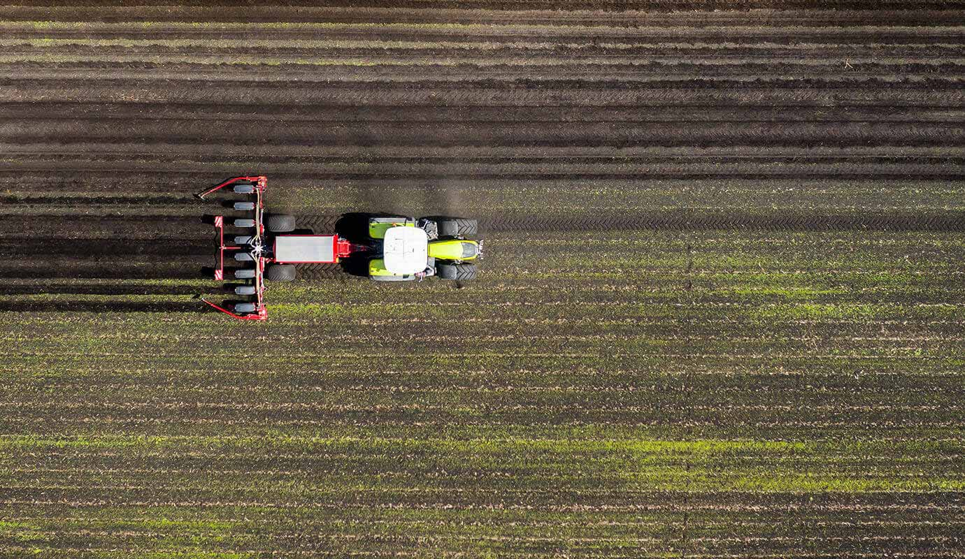 Ariel view of farmland being ploughed with a tractor