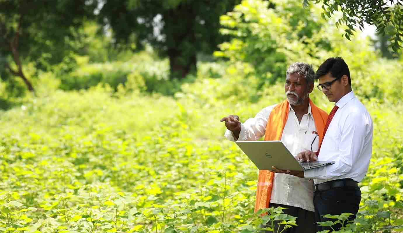 A man with a laptop computer speaks to another among greenery and trees