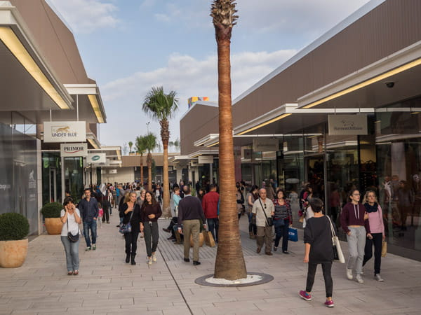 Shoppers walking past palm trees at the Viladecans outlet shopping centre