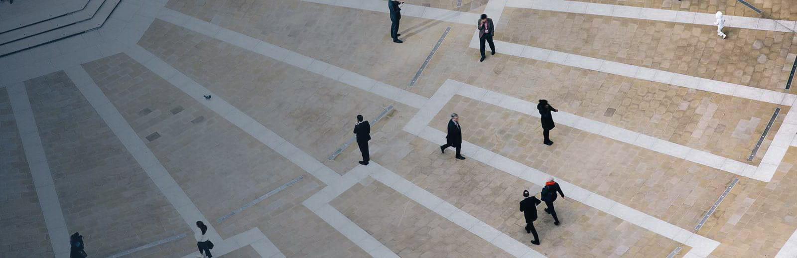 An aerial view of people in suits walking